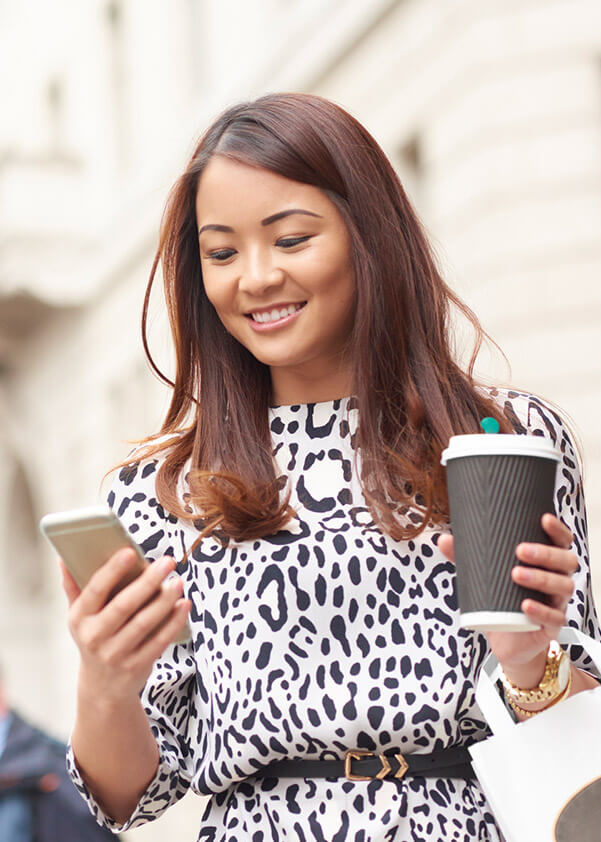Smiling woman holding coffee and cell phone